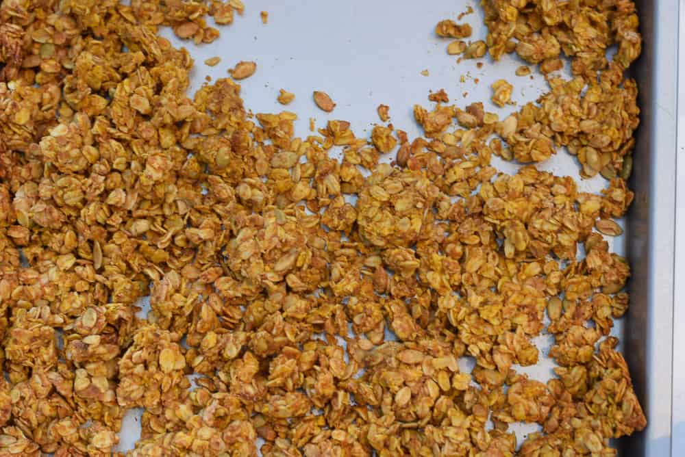 pumpkin seed granola spread out on baking sheet