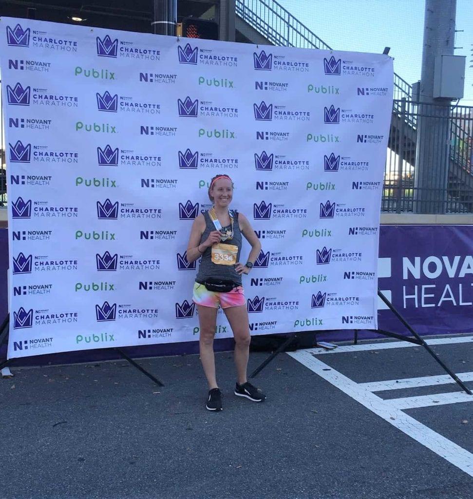 girl holding half marathon race medal in front of Novant Health Marathon backdrop