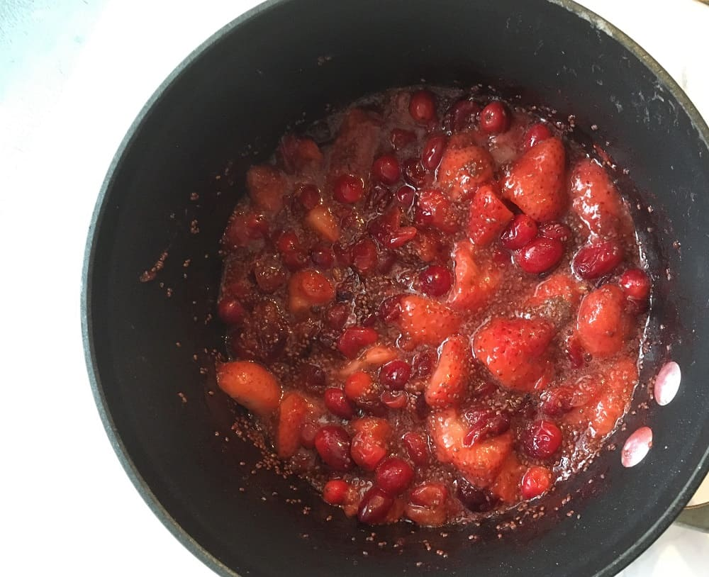 saucepan with cranberries, strawberries, chia seeds and water