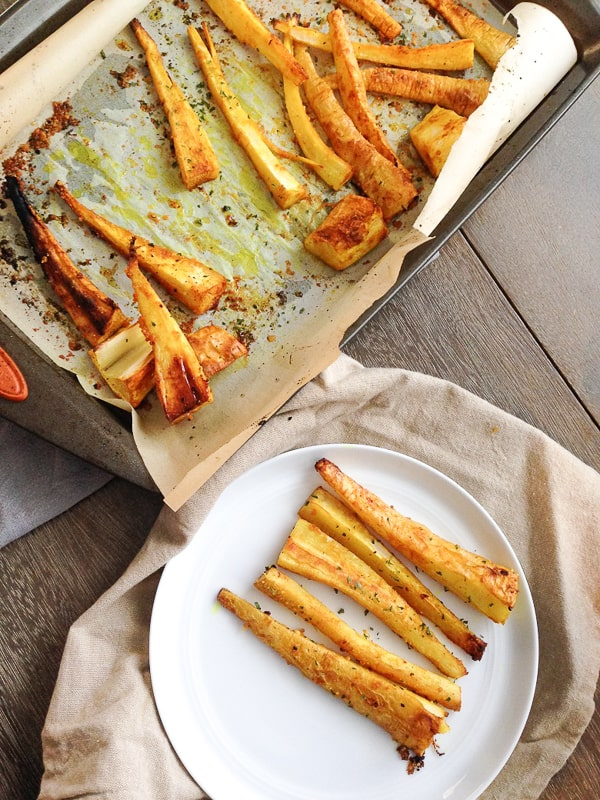 Roasted parsnip fries on a plate seasoned with garlic and turmeric next to baking sheet | Bucket List Tummy