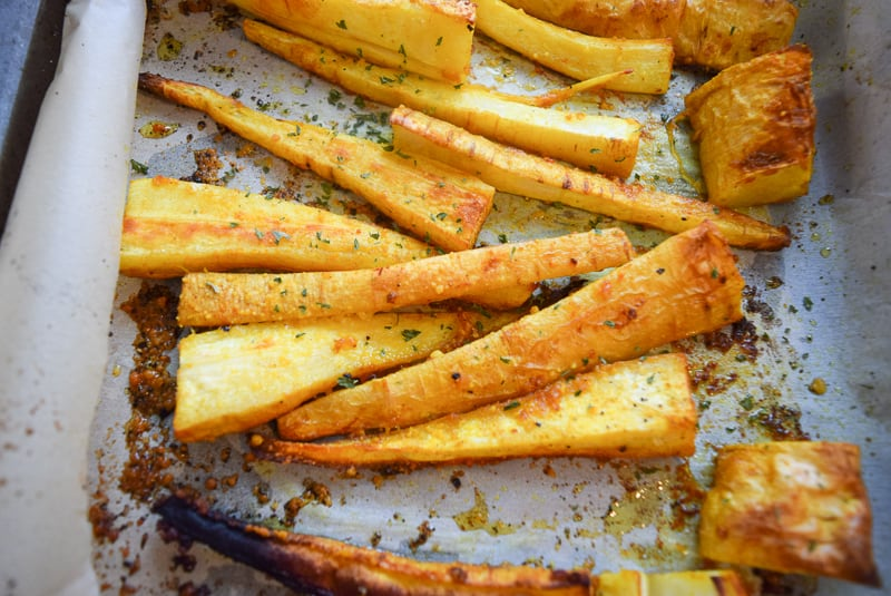 Close up of Roasted parsnip fries on a baking dish seasoned with garlic and turmeric | Bucket List Tummy