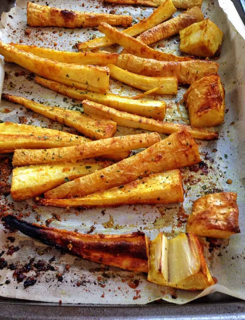 Roasted parsnip fries on a baking dish seasoned with garlic and turmeric | Bucket List Tummy