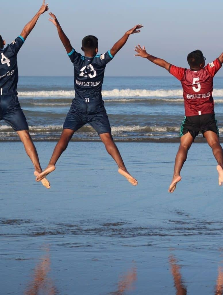 men jumping up in the air on the beach