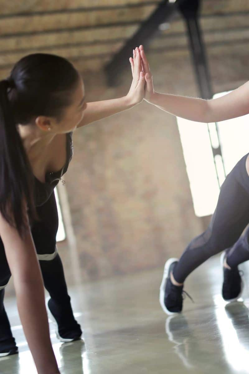 Girl high fiving while doing exercise workout