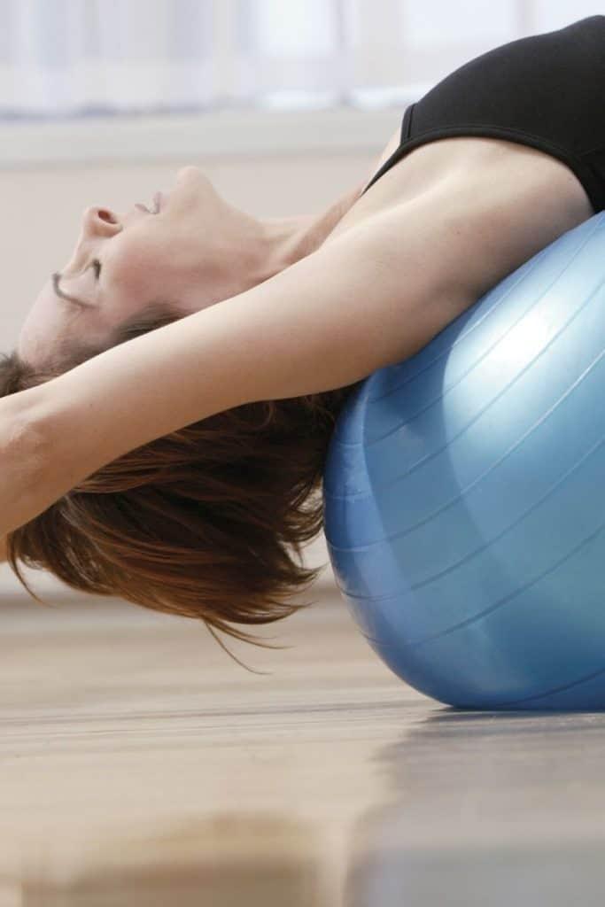 Girl leaning backwards over blue exercise ball