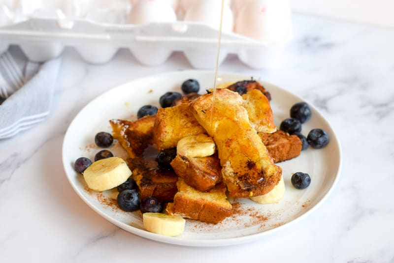 Baby French Toast sticks with syrup, bananas and blueberries on white plate