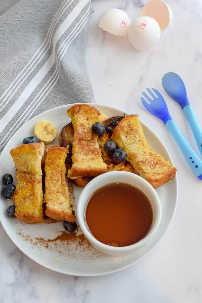 french toast cut into small strips with blueberries and maple syrup on a white plate with gray napkin