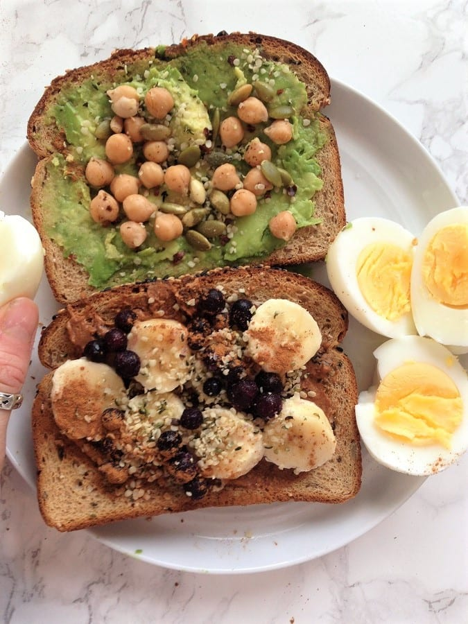 Chickpea toast with hardboiled eggs and toast with fruit on a white plate