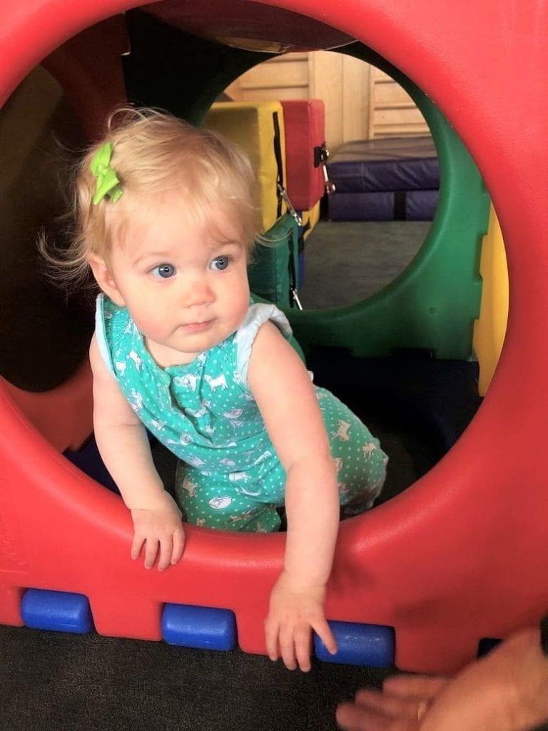 toddler climbing through playpen toy