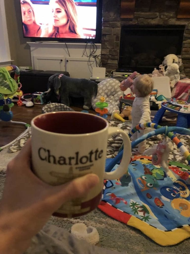 drinking coffee in a room surrounded by baby toys