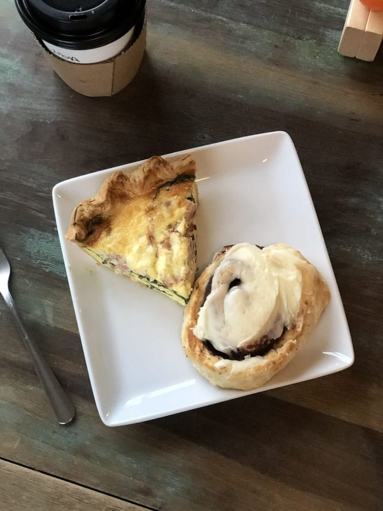 Quiche and cinnamon bun on white plate