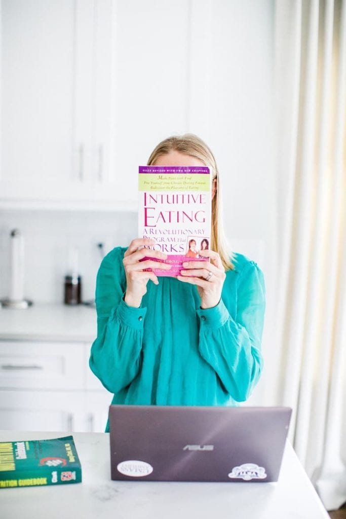 blonde Registered Dietitian holding up Intuitive Eating book