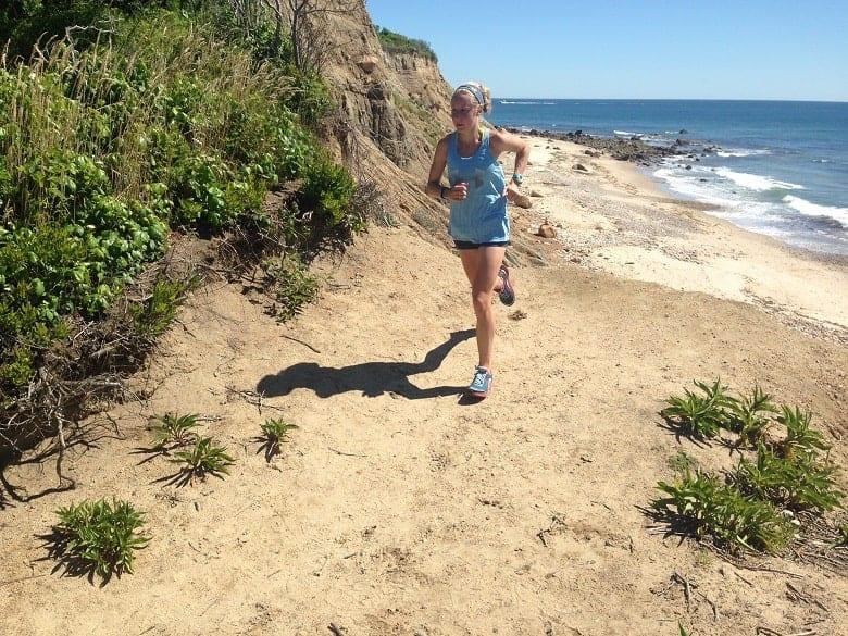 Girl in blue tanktop running on beach in Block Island