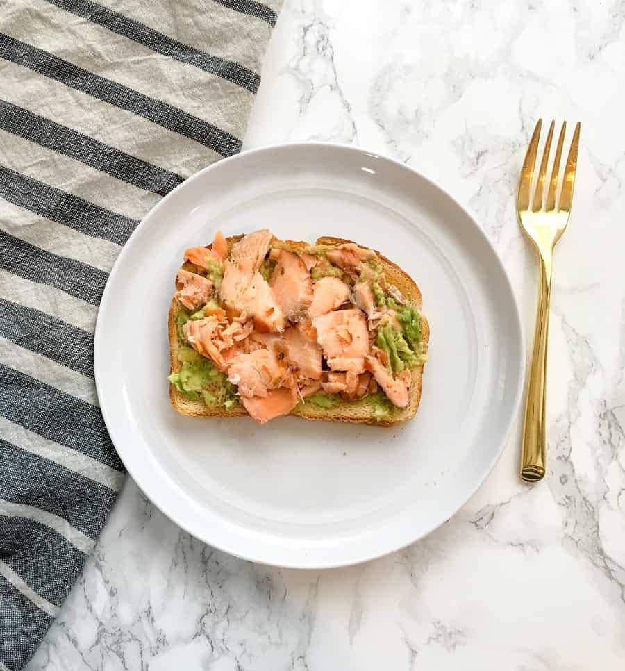 Salmon toast with avocado on a white plate with striped napkin