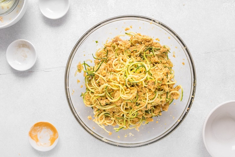 Mixing bowl with spiralized zucchini and canned salmon before cooking