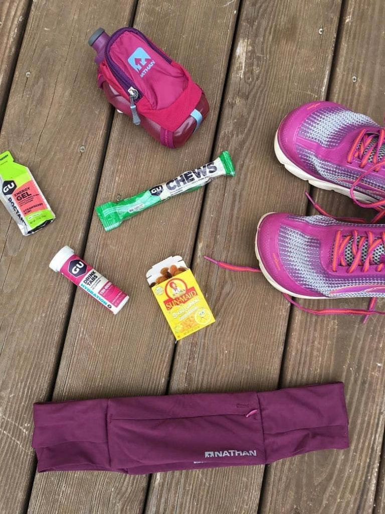 overhead view of different running fuels for marathon nutrition plan on brown background | Bucket List Tummy