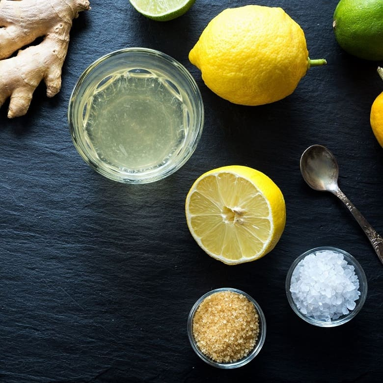 Lemon, salt, sugar on black background to make homemade electrolyte drink, as part of a race day nutrition plan