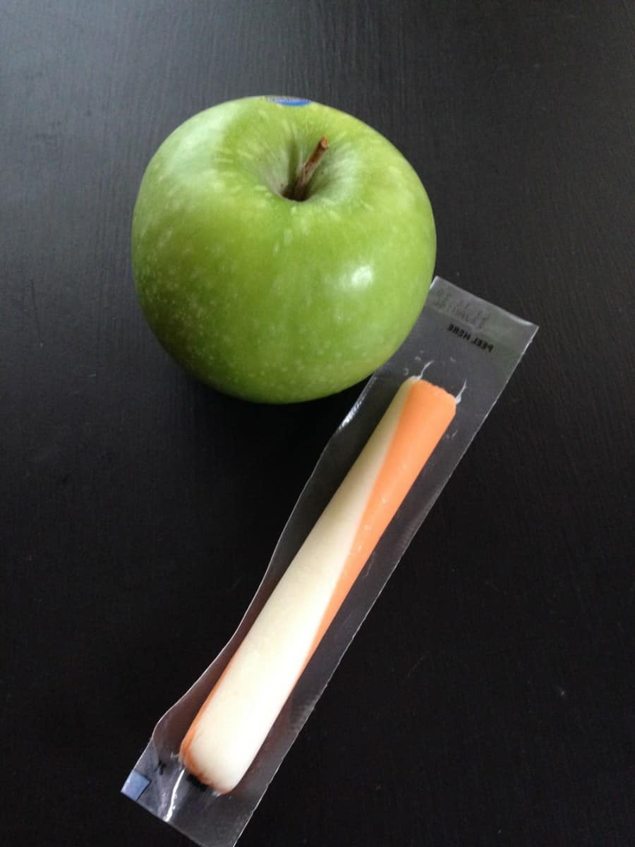 apple and string cheese on black table