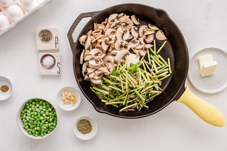 Skillet with asparagus and mushrooms on white table with bowl of peas and spices
