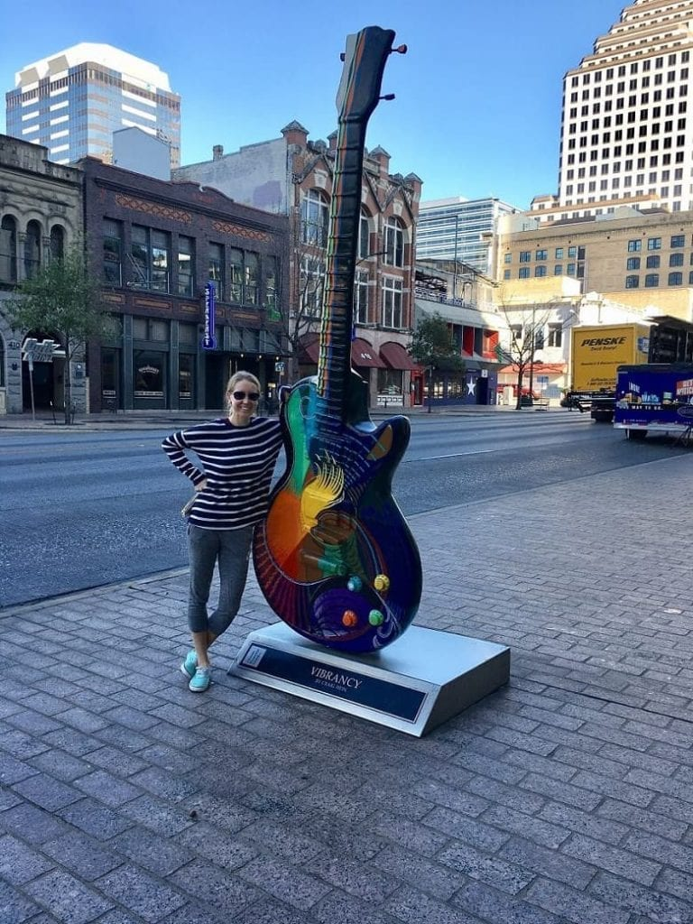 girl leaning on guitar in downtown Austin, Texas