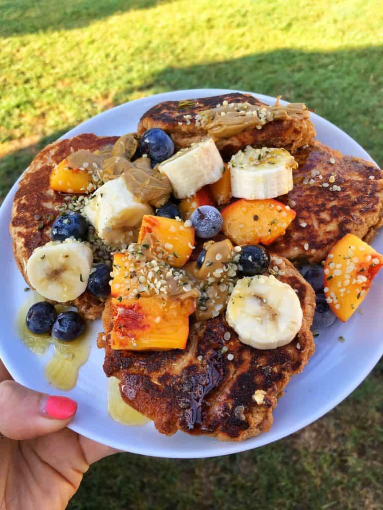 pancakes with fruit, hemp seeds on white plate