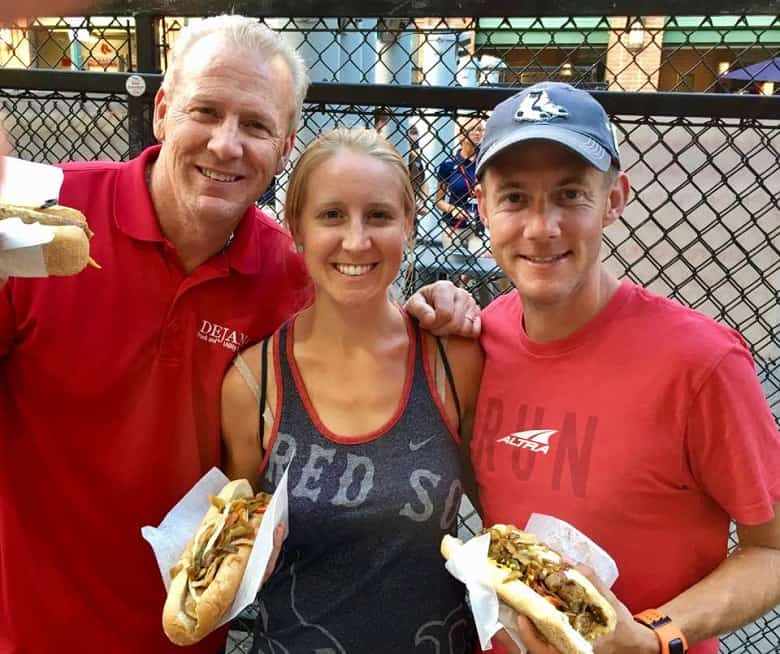 Father, daughter and husband enjoying sausages at Fenway Park