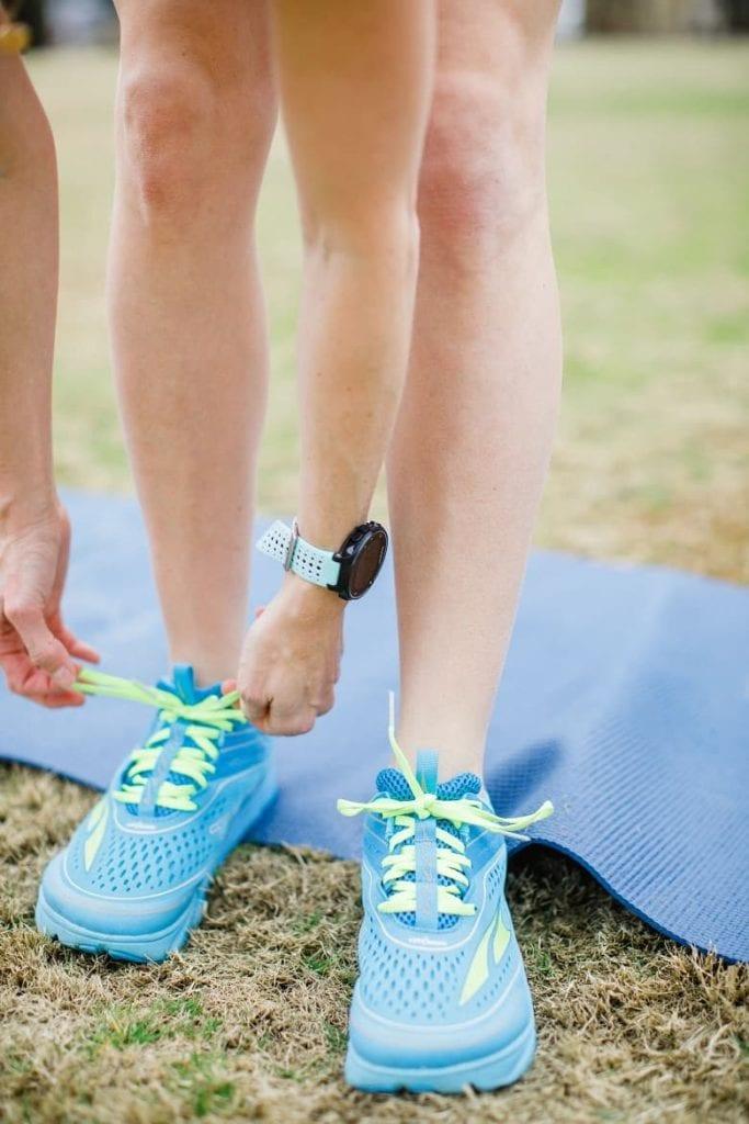 runner bending down to tie her shoe