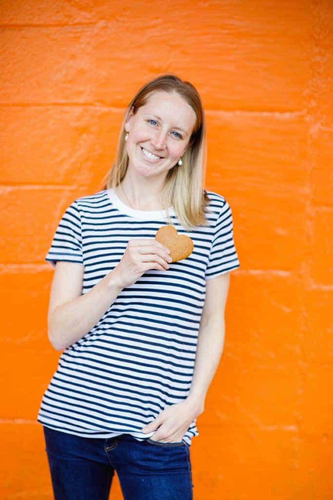 Girl holding cookie in front of orange wall | Bucket List Tummy