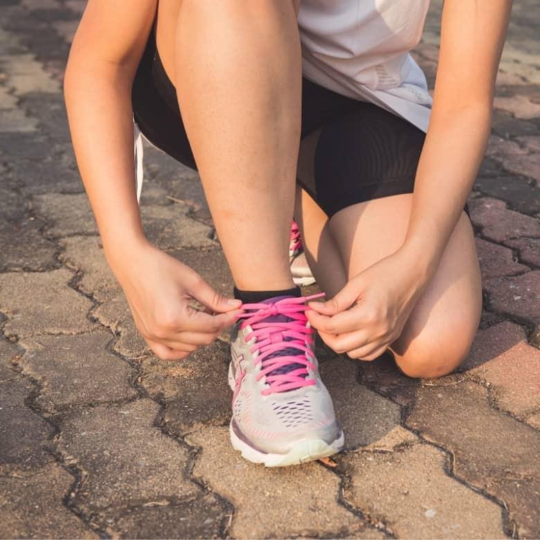 Runner bending down to tie shoe