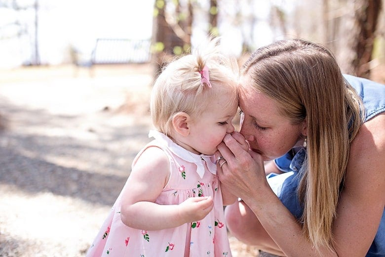 Mom Smelling flowers at park with baby girl