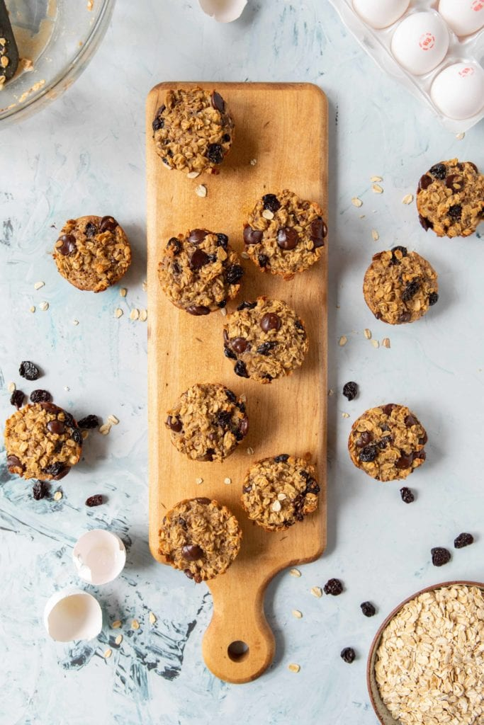 Baked Oatmeal Cups on wooden serving platter with chocolate chips scattered | Bucket List Tummy