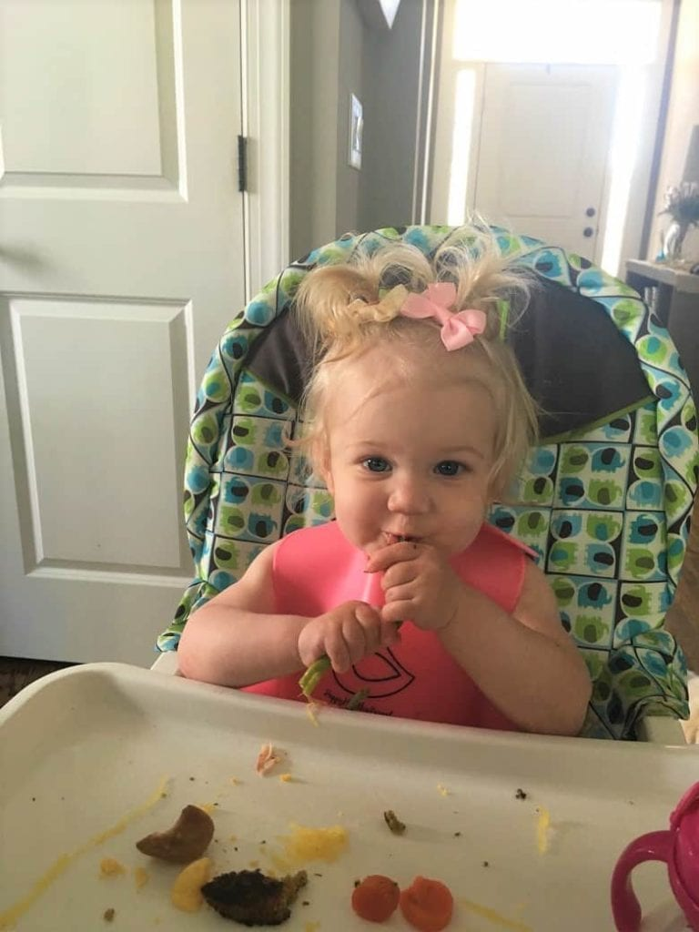 Baby in Highchair eating asparagus