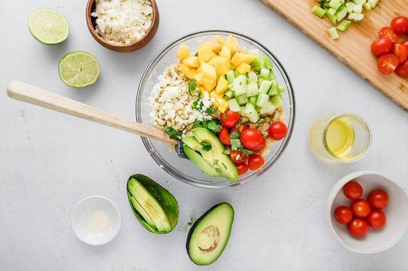 Mango Quinoa Salad for cold weather, topped with avocado, tomatoes, cucumbers