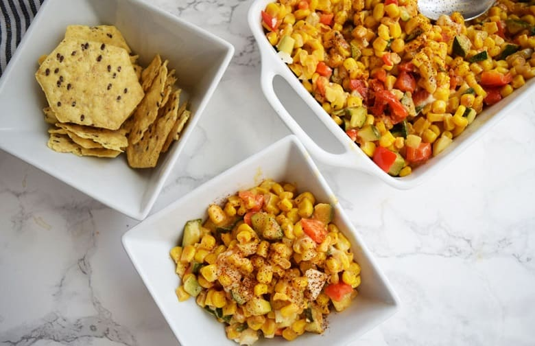 Zucchini Mexican Street Corn in a serving dish and bowl with chips