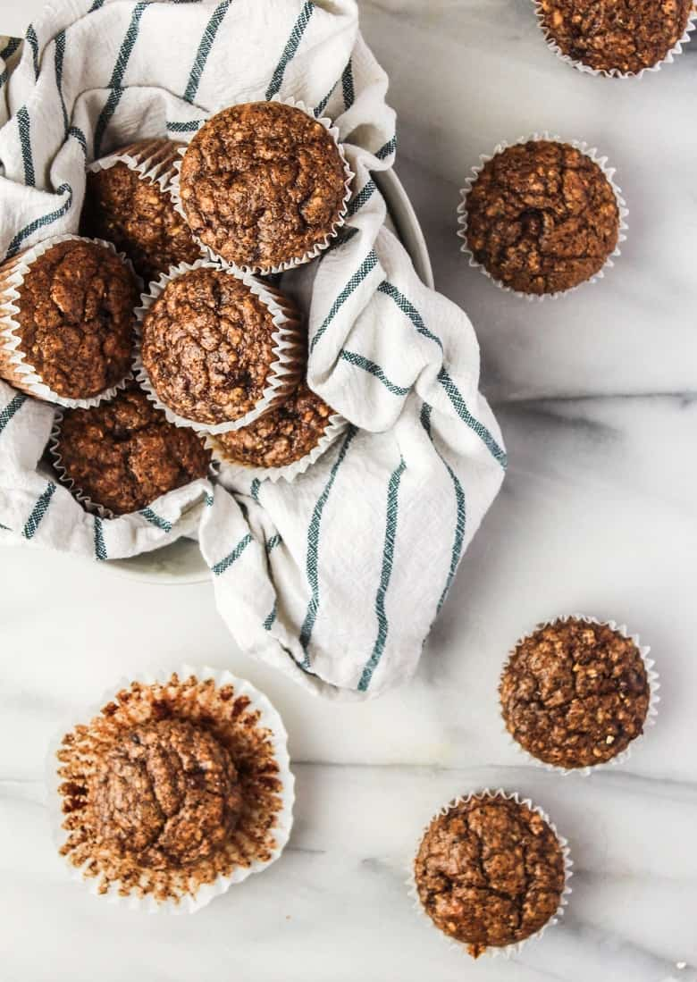 Banana Muffins in bowl with kitchen towel and on white countertop