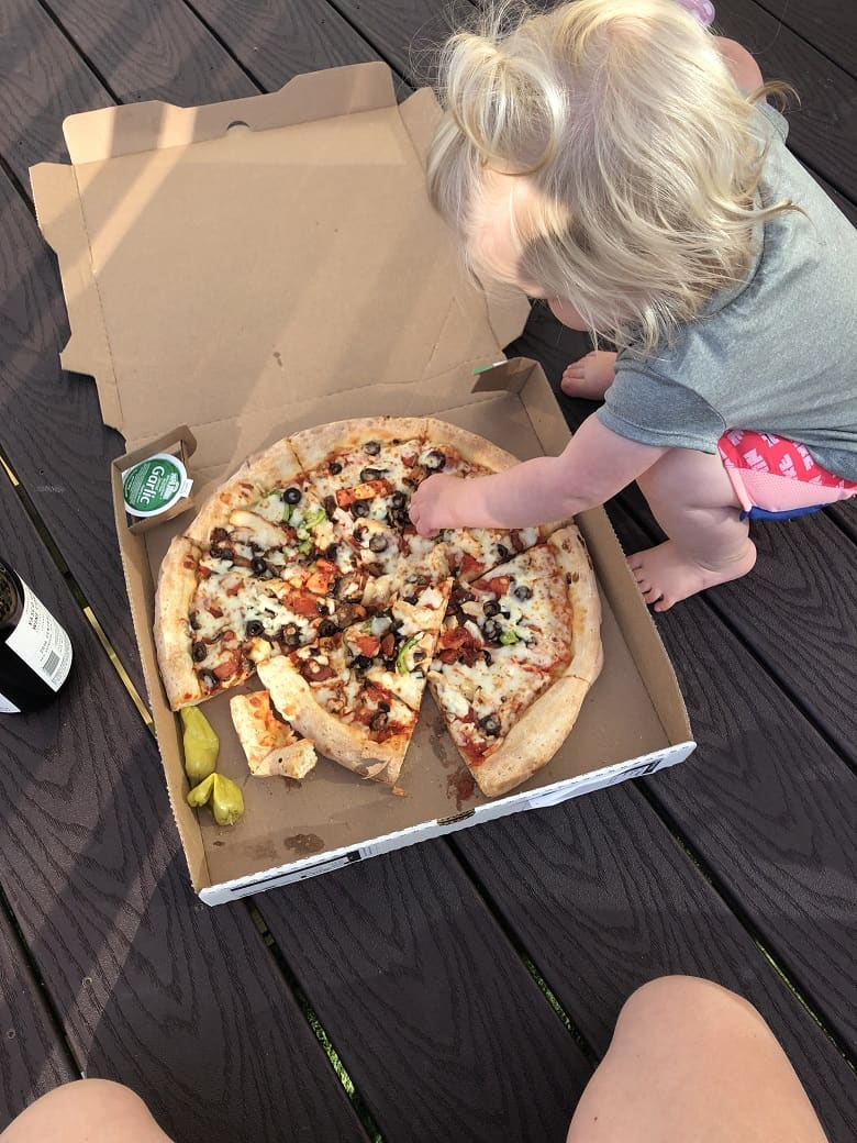 toddler picking toppings off of pizza on outside deck