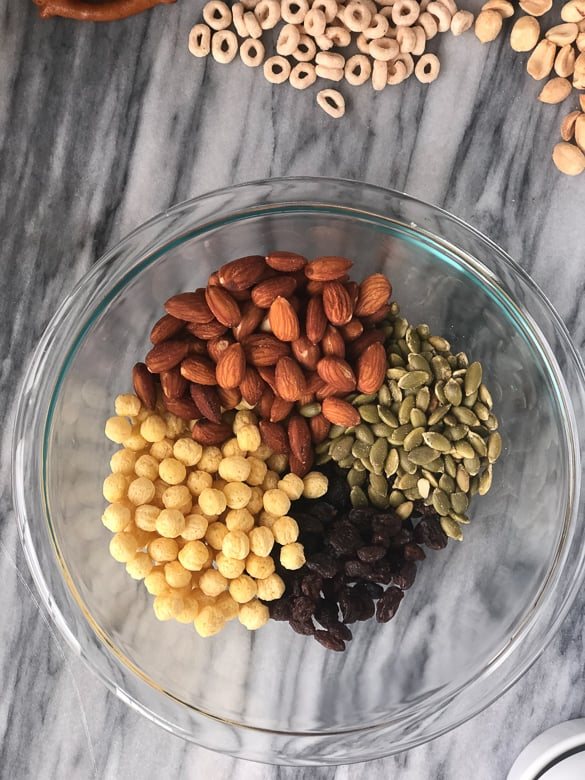 pumpkin seeds, almonds, kix and raisins in a bowl for homemade trail mix