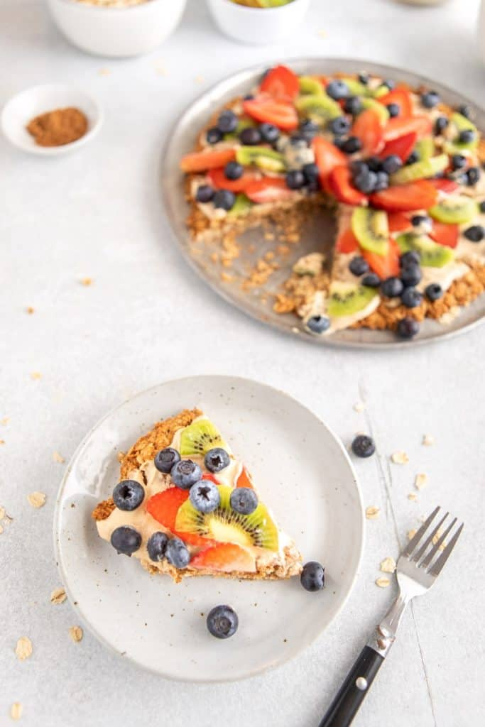 Slice of breakfast fruit pizza on white plate with fork | Bucket List Tummy