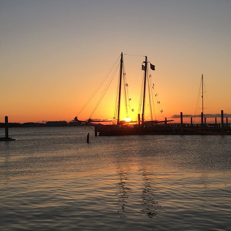 Charleston, SC sunset with a sailboat in front of it
