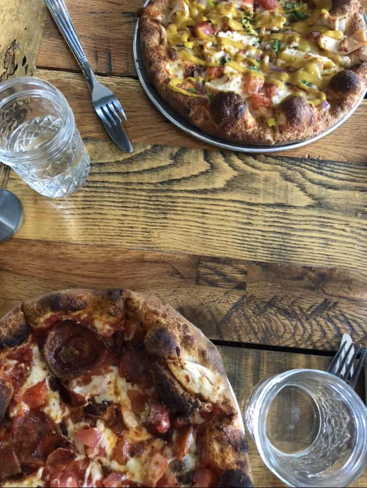 overhead table view of pizza and water