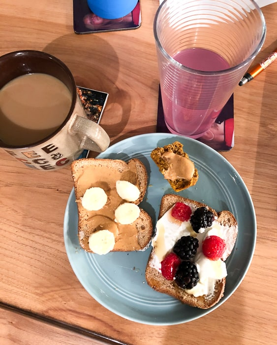 toast with fruit and a muffin on blue plate with coffee and electrolytes water