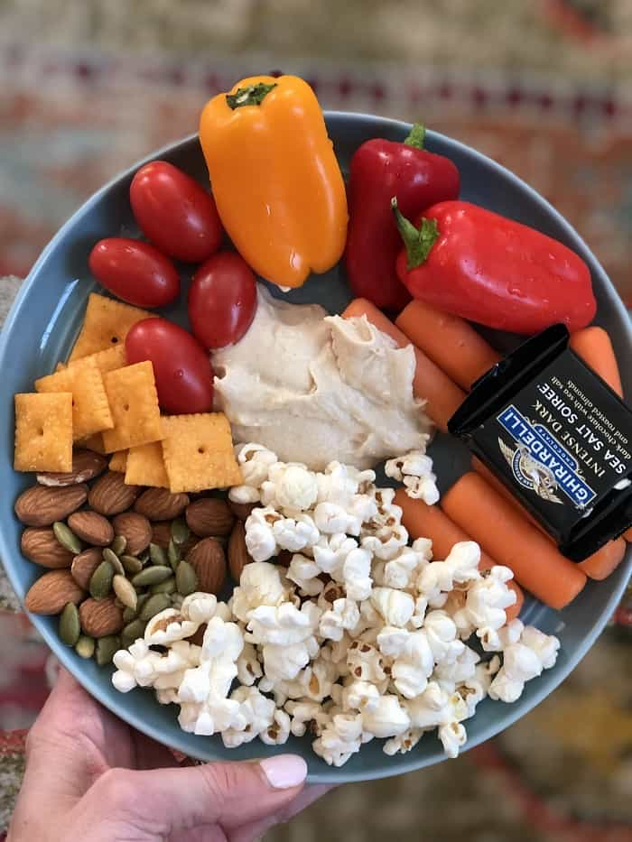 snack plate with popcorn, peppers, tomatoes, almonds, carrots, chocolate
