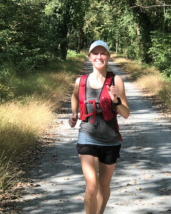 Girl smiling on a trail wearing a running vest