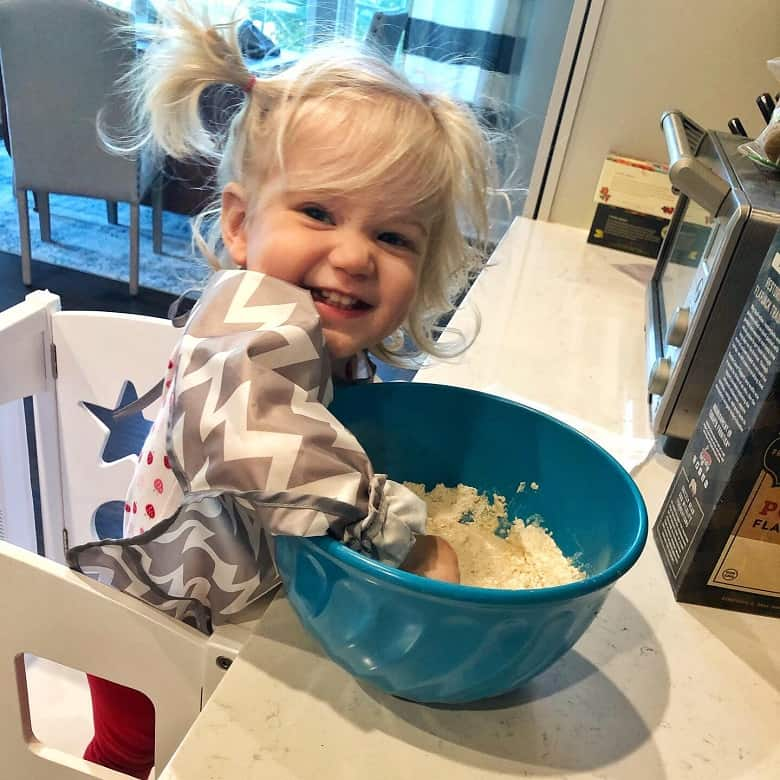 toddler using mixing bowl in the kitchen