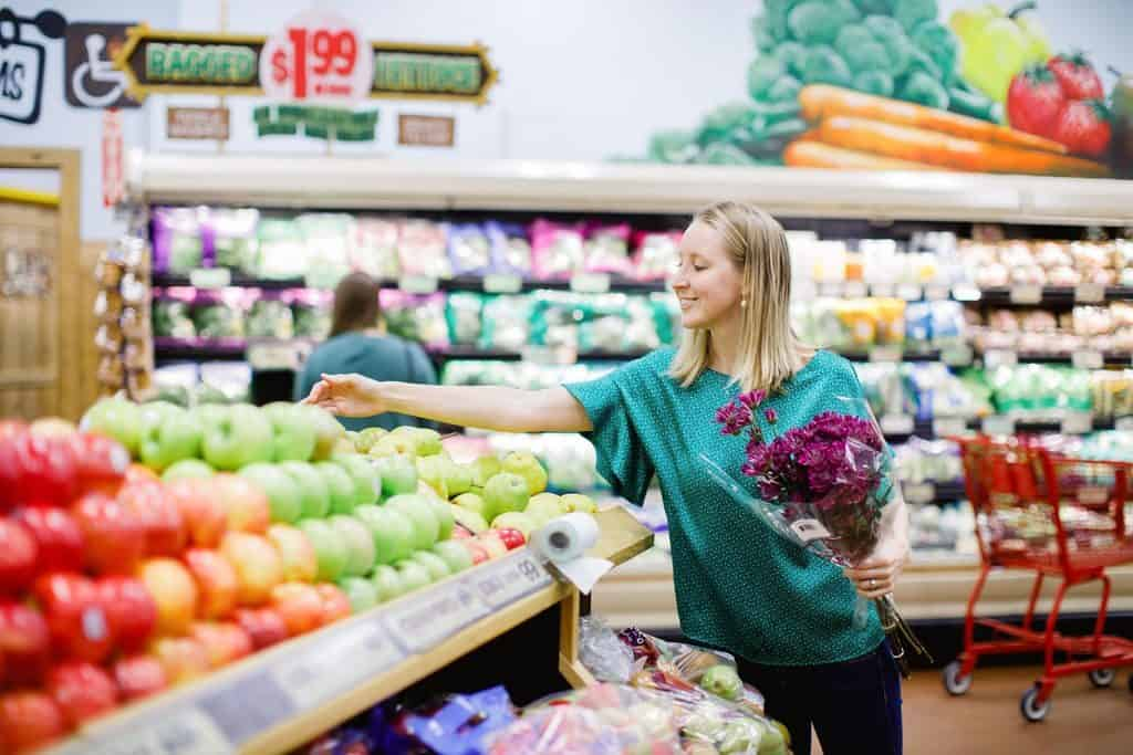 Girl in grocery store looking at produce and holding purple flowers