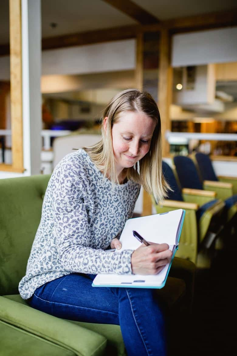 Girl writing in journal to study on green chair