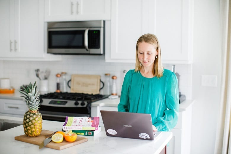 Girl on laptop in kitchen with cutting board and fruit next to her