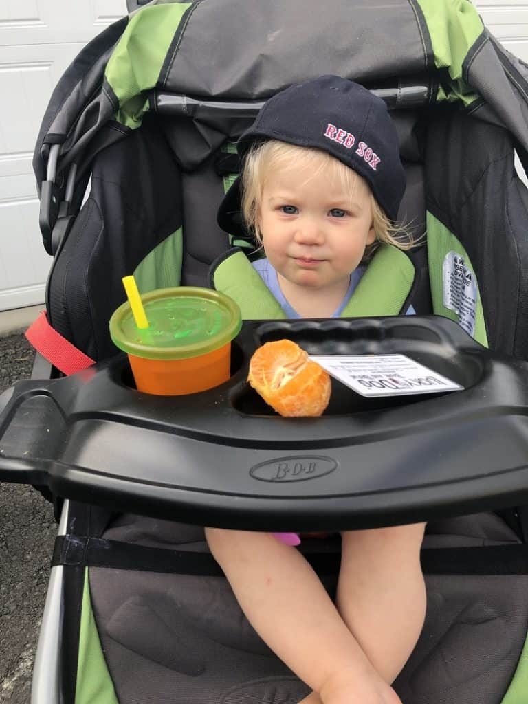 baby in stroller with clementine