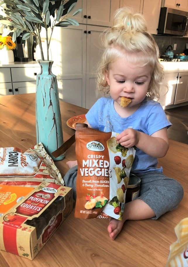Toddler eating Sprouts VEggie Crisps on kitchen table