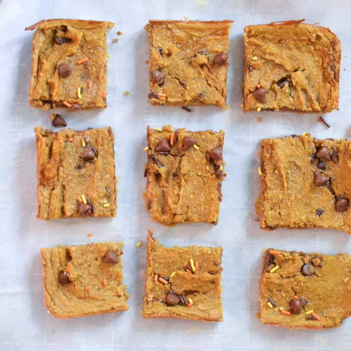 Freshly baked Vegan Pumpkin Blondies with chocolate chips cut into 9 squares on parchment paper